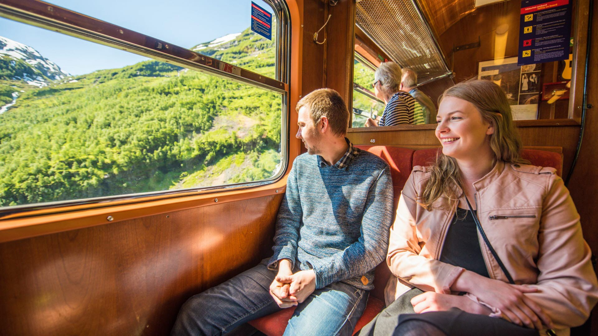 Young man and woman sitting onboard The Flåm Railway in summer looking out. Elderly couple standing looking out the windows.